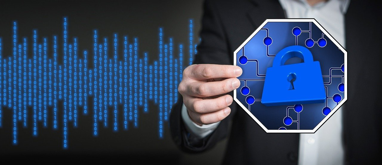 Businessman holds graphic representing software security in front of matrix code screen