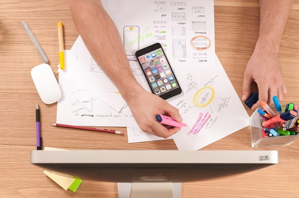 Aerial view of workdesk with screen papers mobile phone and hands making notes