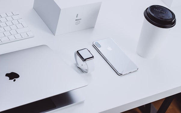 Apple laptop Apple watch Apple iPhone coffee mug on white desk