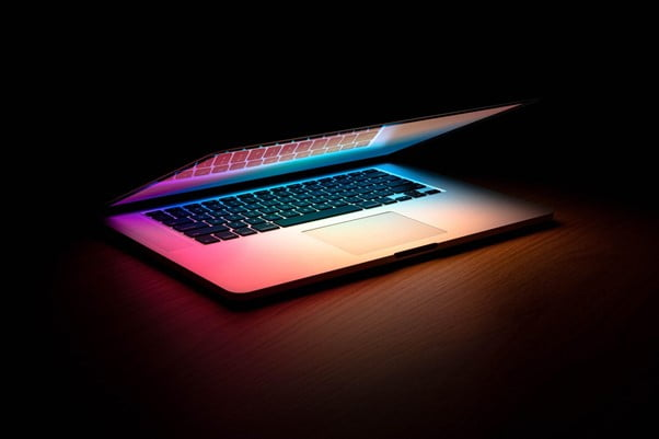 Half open laptop glows pink and purple hues from screen against black background
