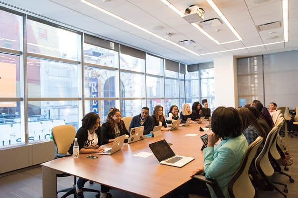 Stakeholders sit around boardroom table in boardroom with laptops open