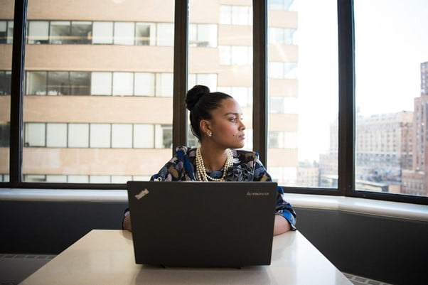 Young woman sits in front of laptop in office looking out of the window at city skyscrapers
