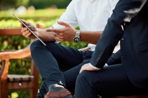 Two businessmen sit on a bench outside discussing something on a tablet screen