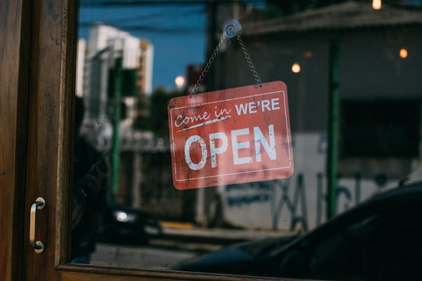 Shop sign behind glass shop door of a small business reads Come in We're Open