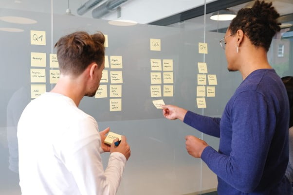 Product manager talks to product owner in front of a project planning board in an office